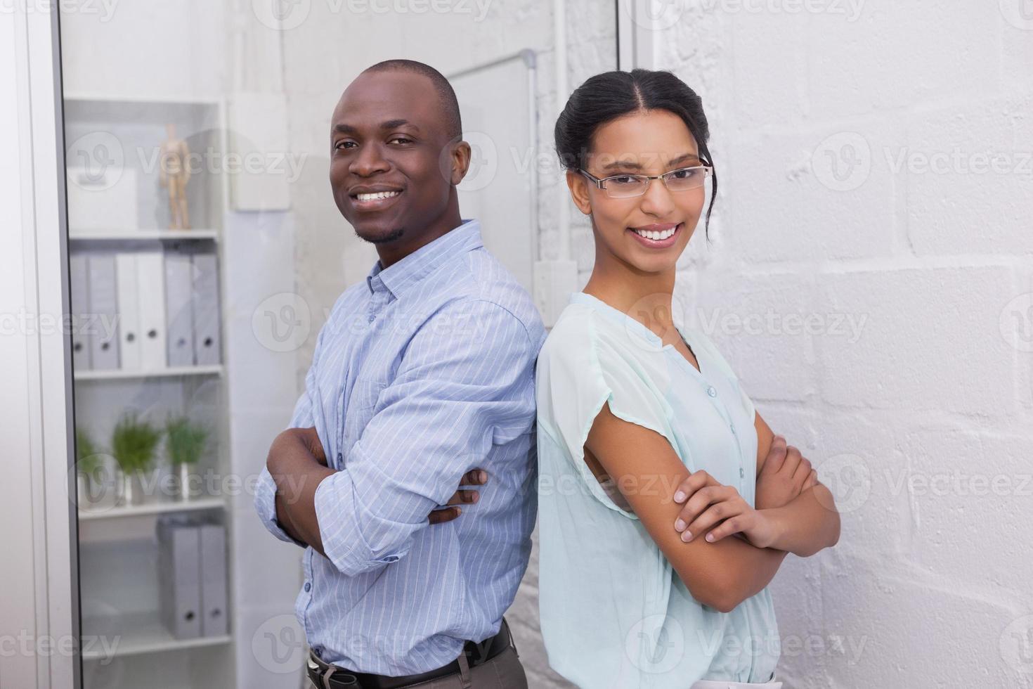 sorridenti uomini d'affari con le braccia conserte foto