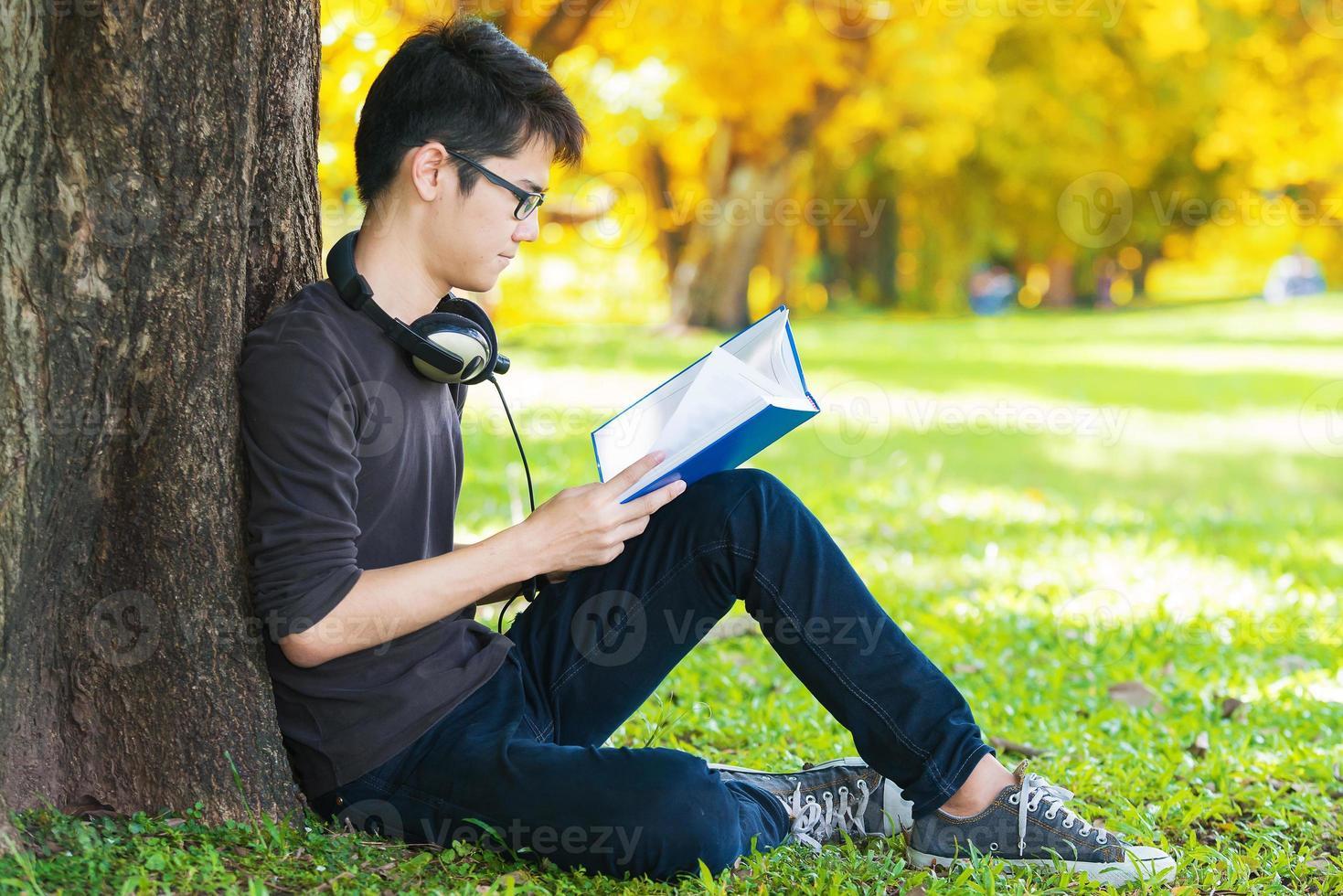 uomo che legge il libro nel parco, seduto sotto un albero foto