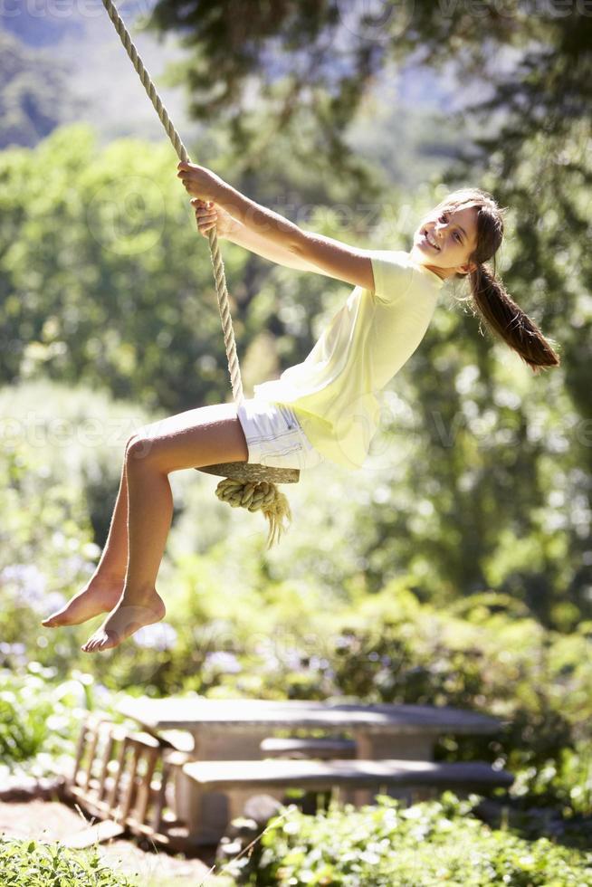 giovane ragazza divertirsi sull'altalena di corda foto