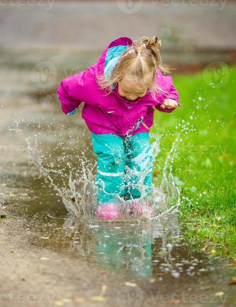 la bambina felice gioca in una pozzanghera foto