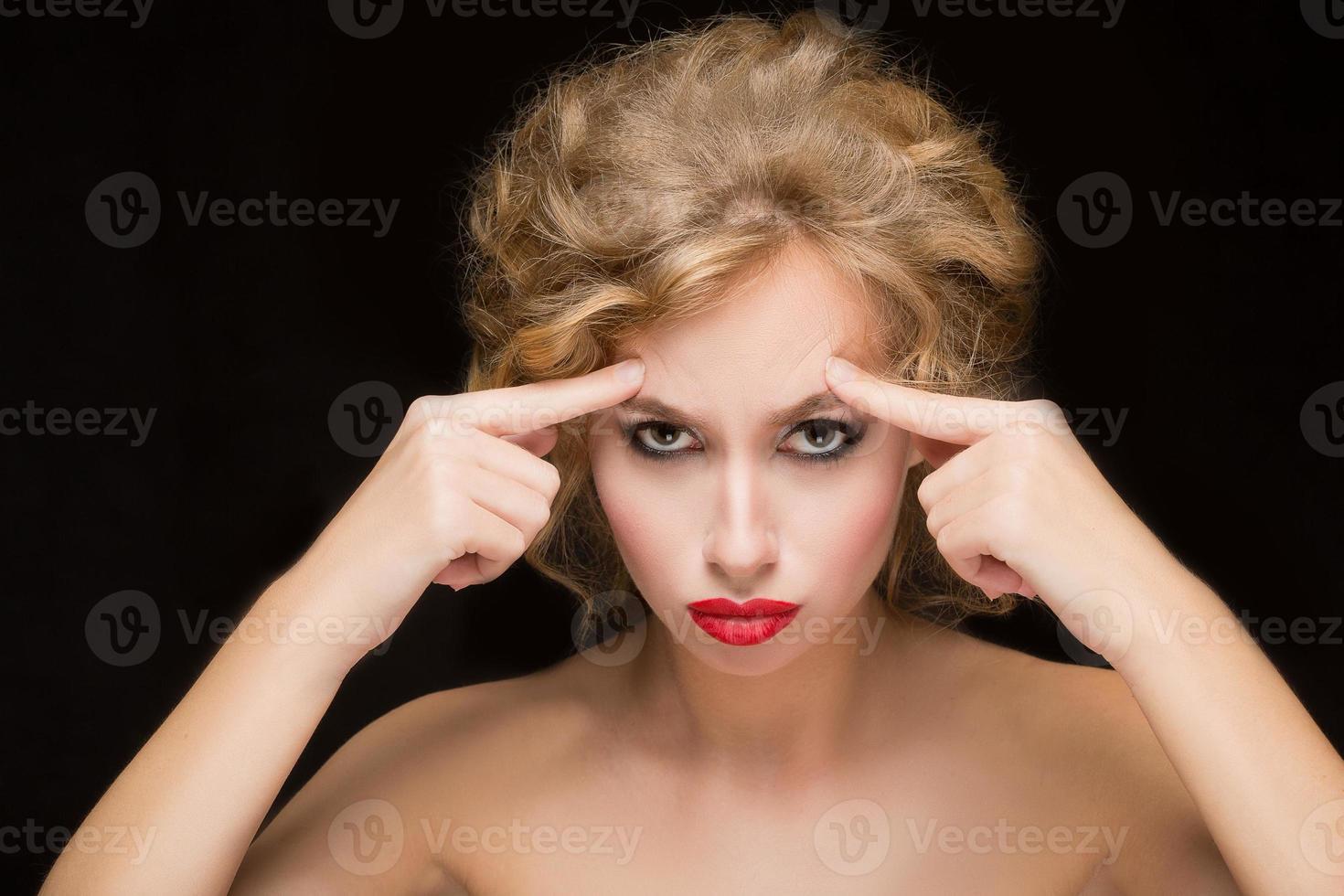 volto di una bella donna che punta alla sua fronte foto
