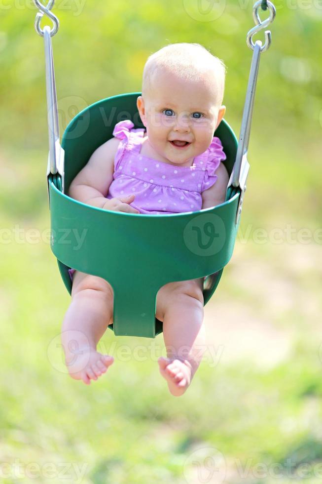 bambina felice oscillante al parco giochi foto