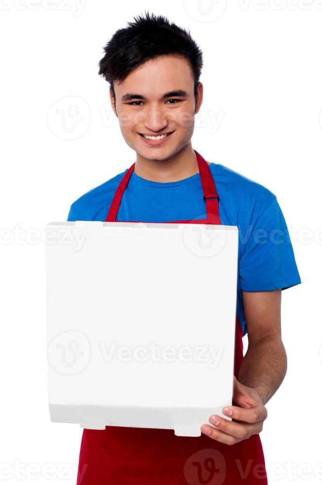 ragazzo in possesso di una scatola per pizza aperta foto