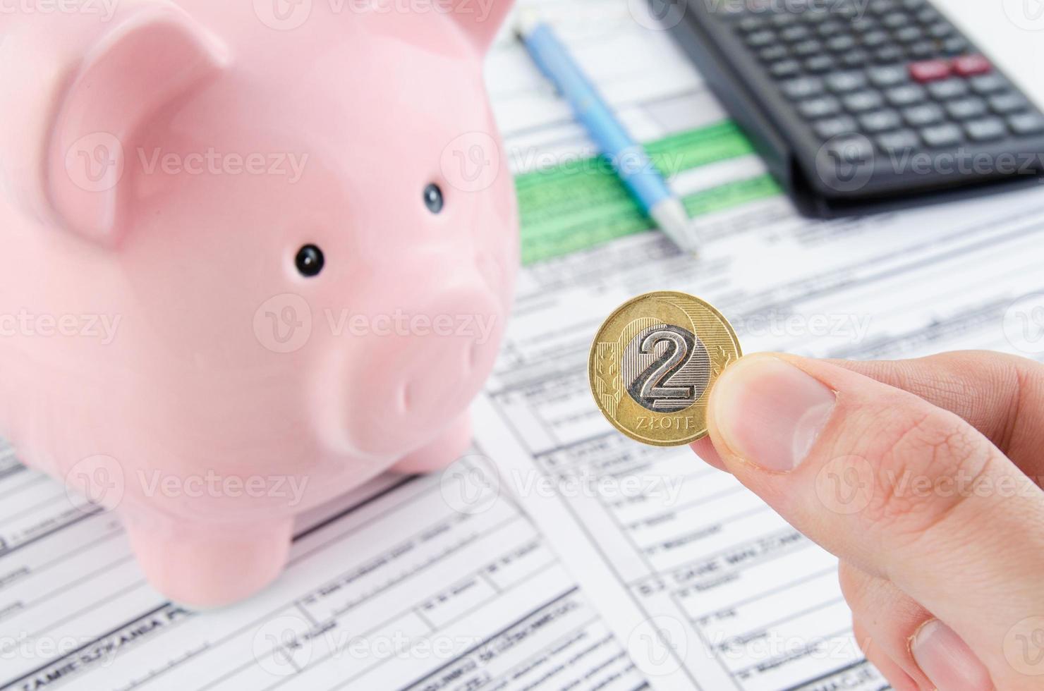 mano che tiene la moneta polacca. moduli di imposta sul reddito polacco foto