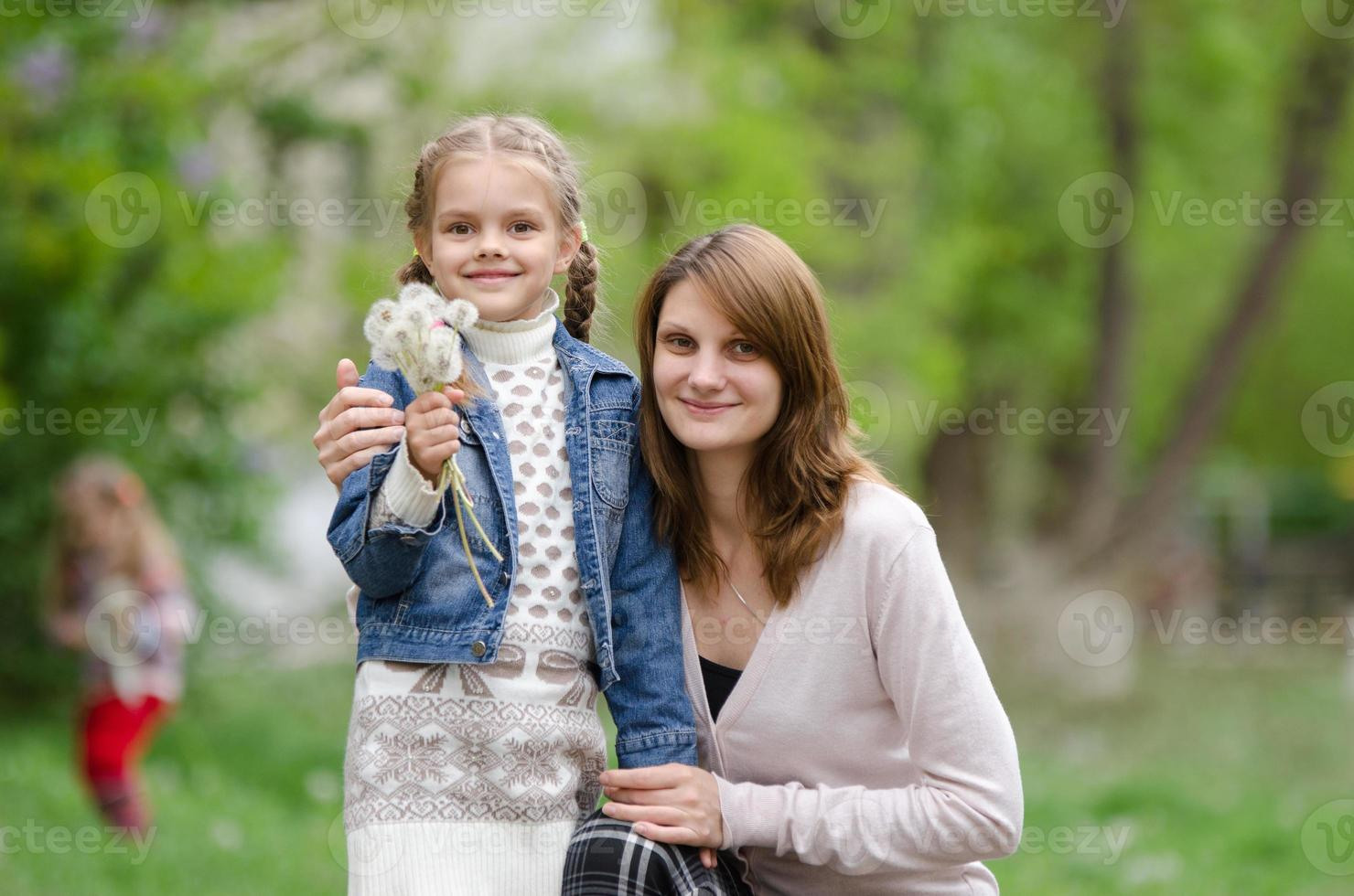 la giovane donna abbraccia sua figlia con i denti di leone foto