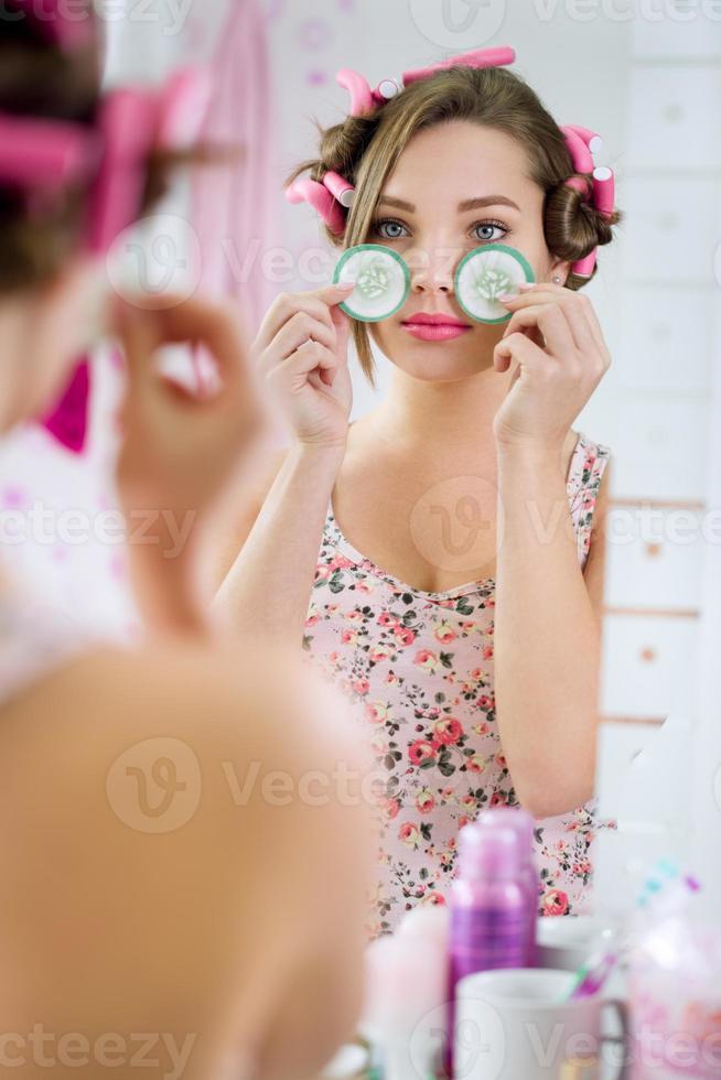 giovane donna in accappatoio con cetriolo sugli occhi foto