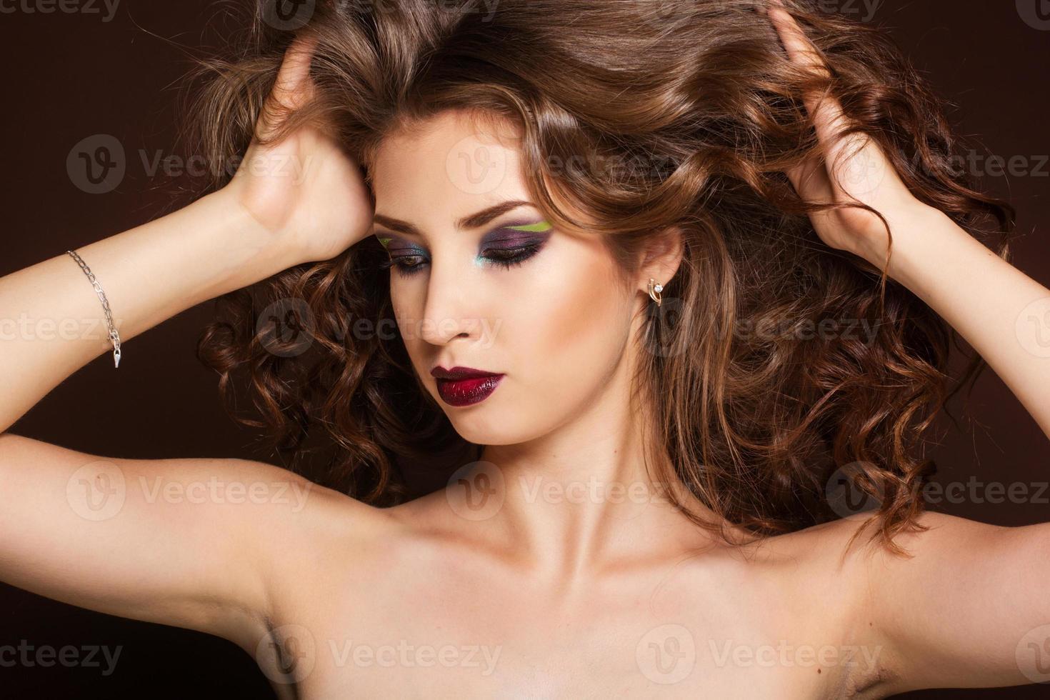bella ragazza bruna con i capelli ricci sani foto