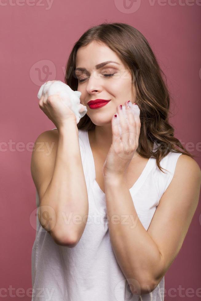 donna con una bottiglia di lozione foto