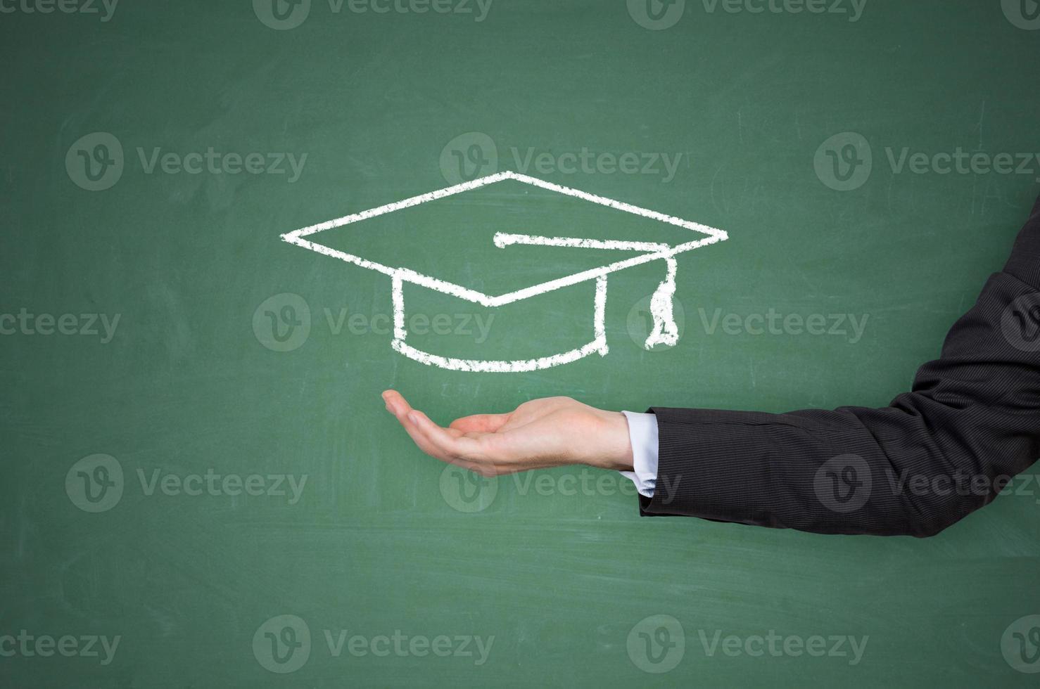 mano che tiene il cappello di laurea foto
