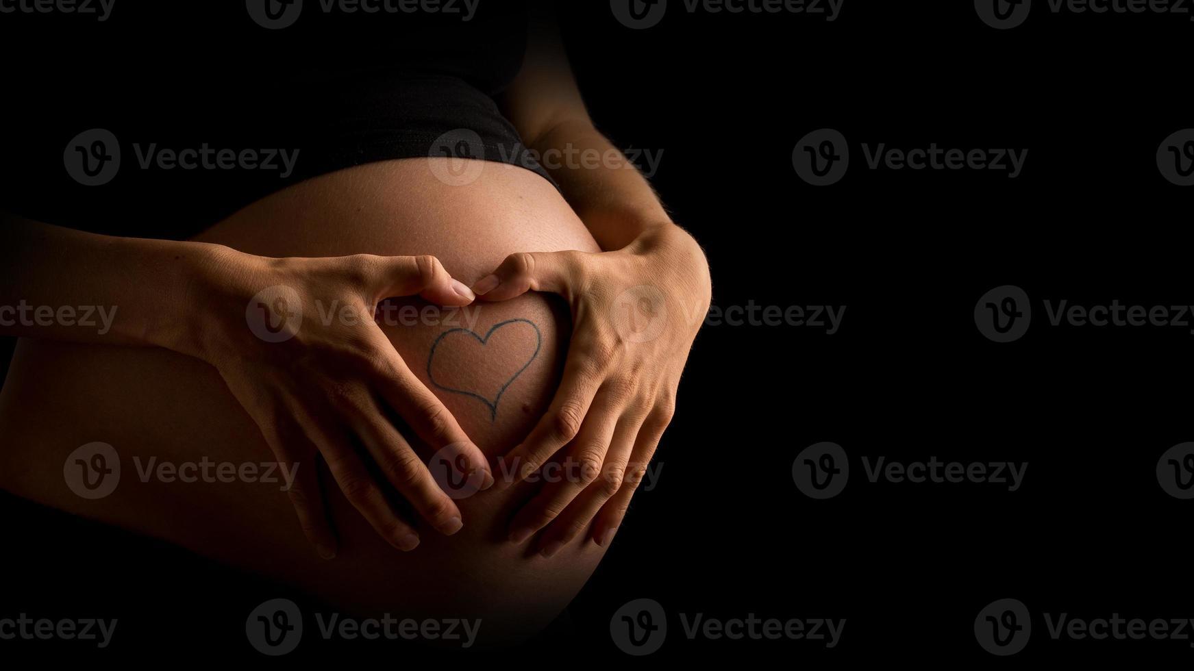 donna incinta che mostra il tatuaggio del cuore sulla pancia foto