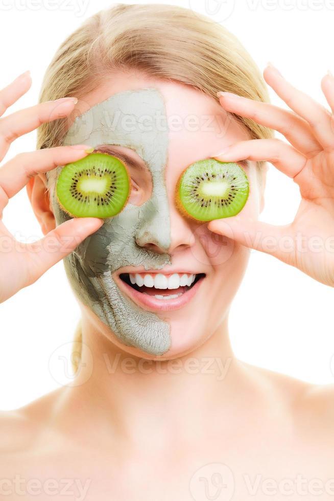 cura della pelle. donna in maschera di argilla con kiwi sul viso foto