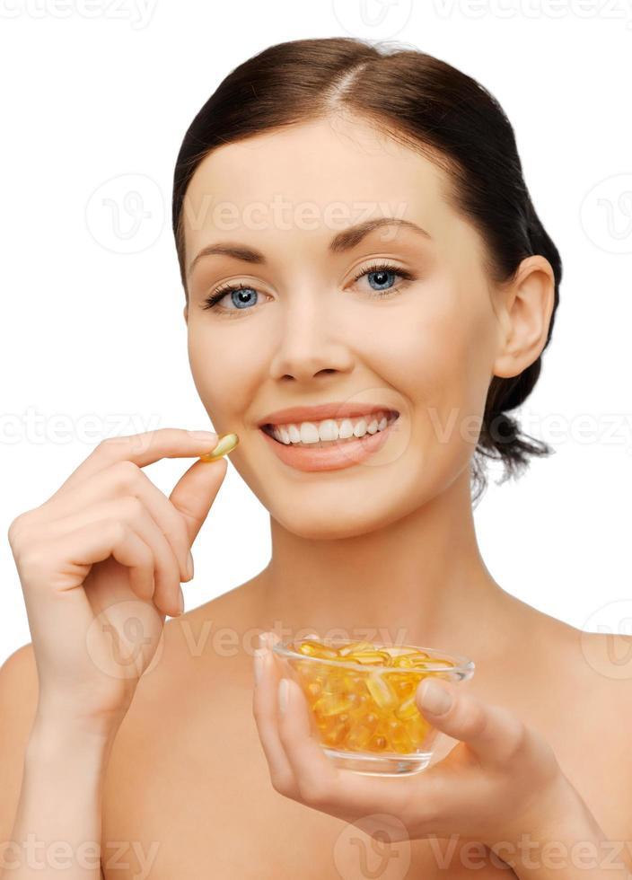 donna felice con capsule di olio di omega 3 foto