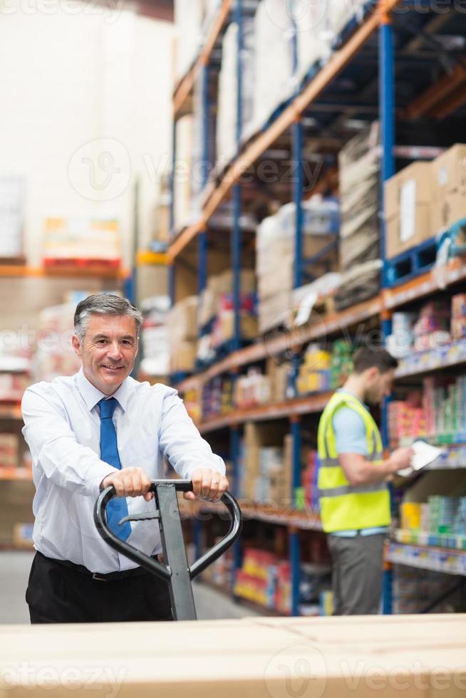 manager tirando il carrello con le scatole di fronte al suo dipendente foto