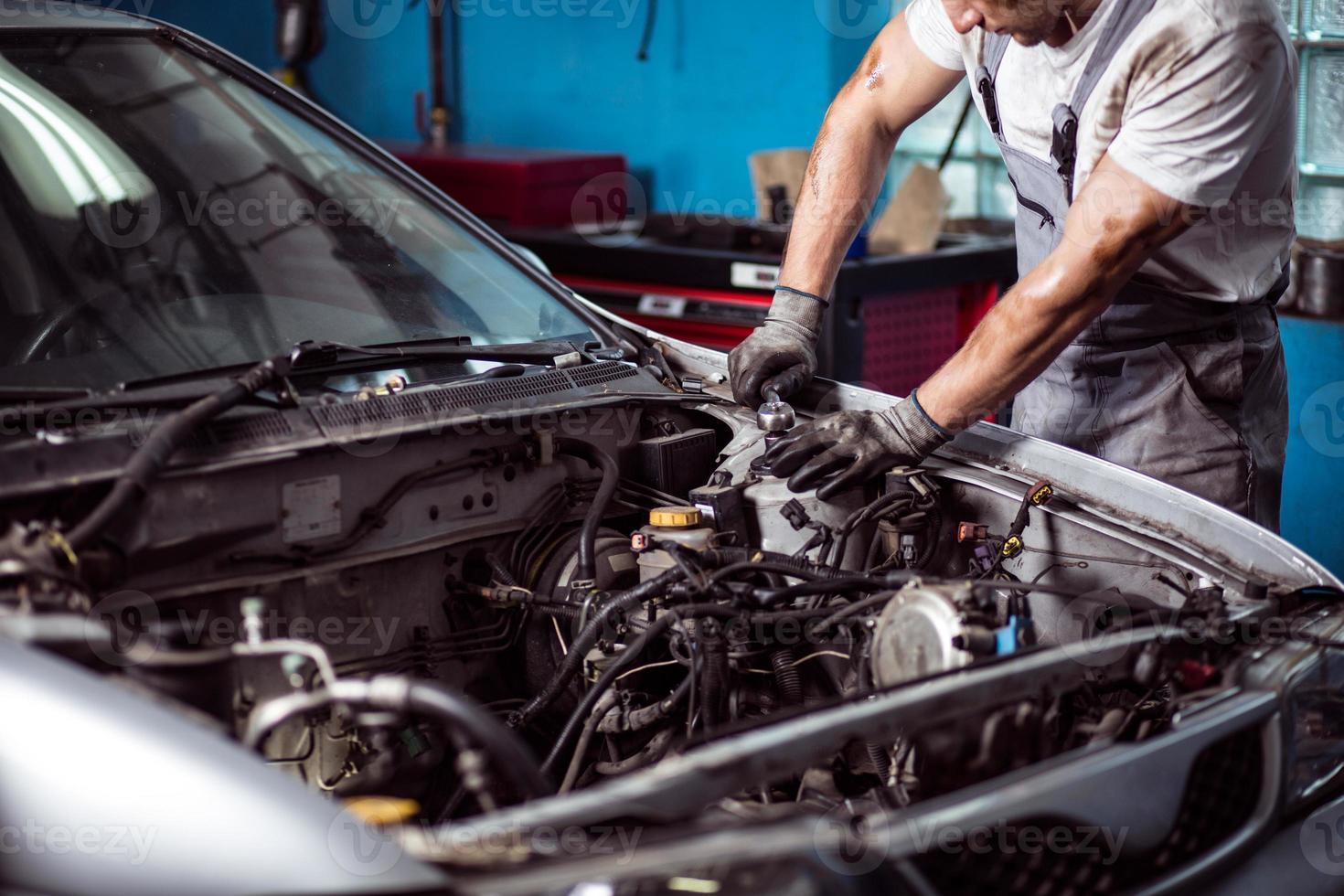 meccanico che mantiene il motore dell'auto foto