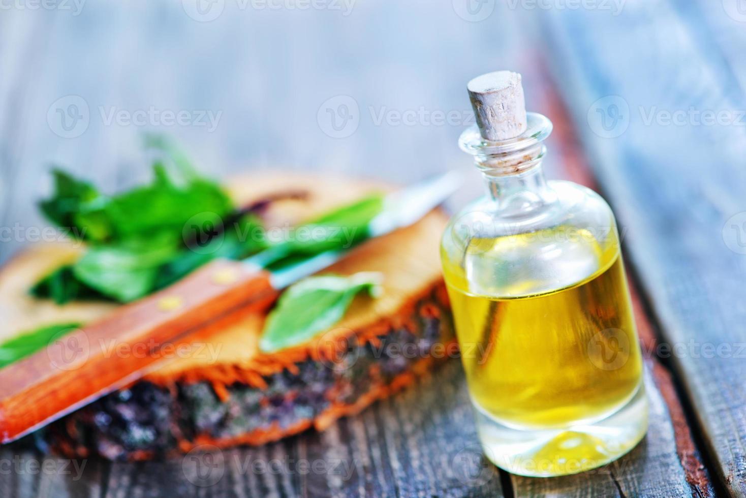 olio di menta posizionato accanto a foglie tritate sul tavolo di legno foto