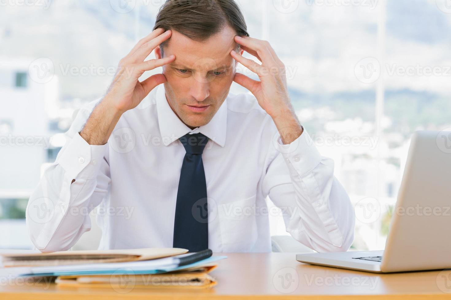 uomo d'affari preoccupato che tiene la sua testa foto