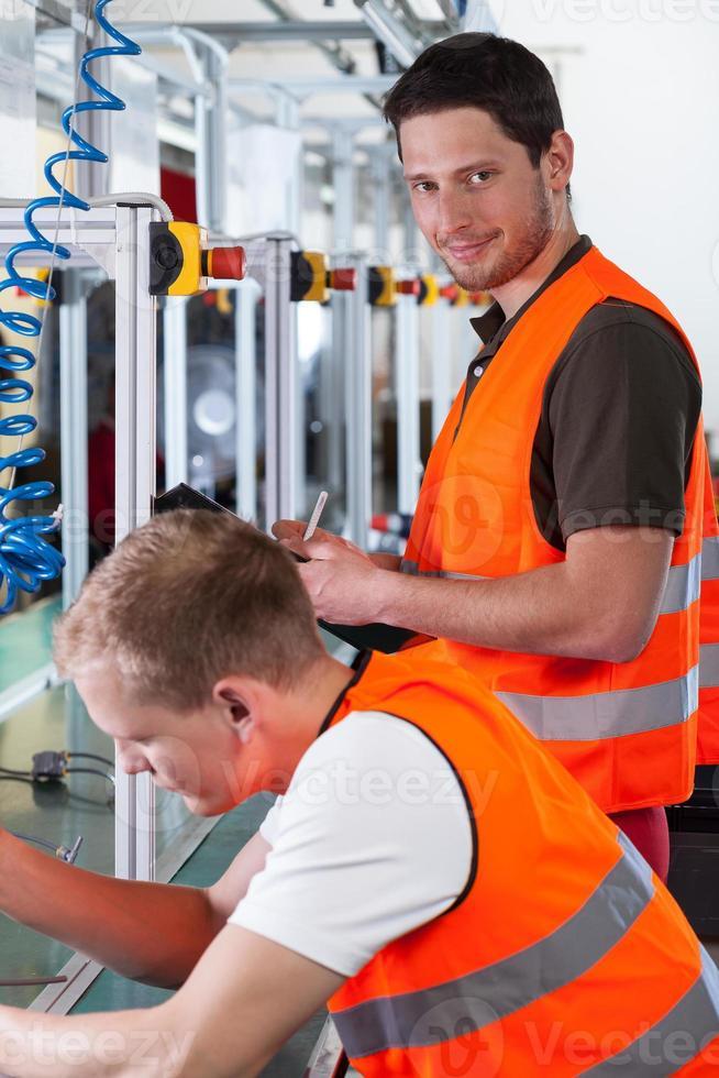 lavoratori vicino alla linea di produzione foto
