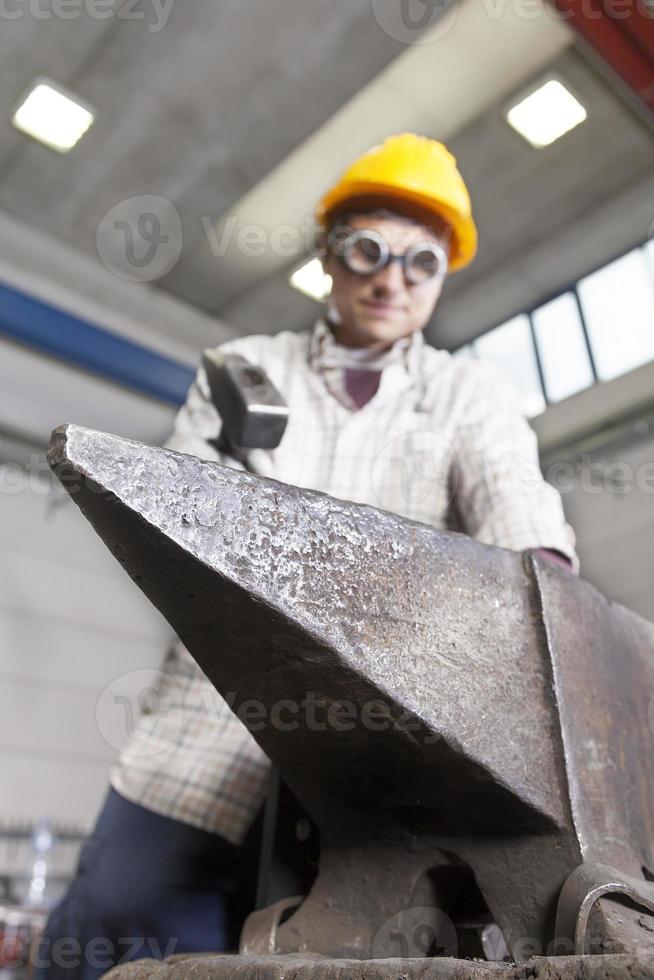 il metalmeccanico lavora il metallo con il martello sull'incudine foto