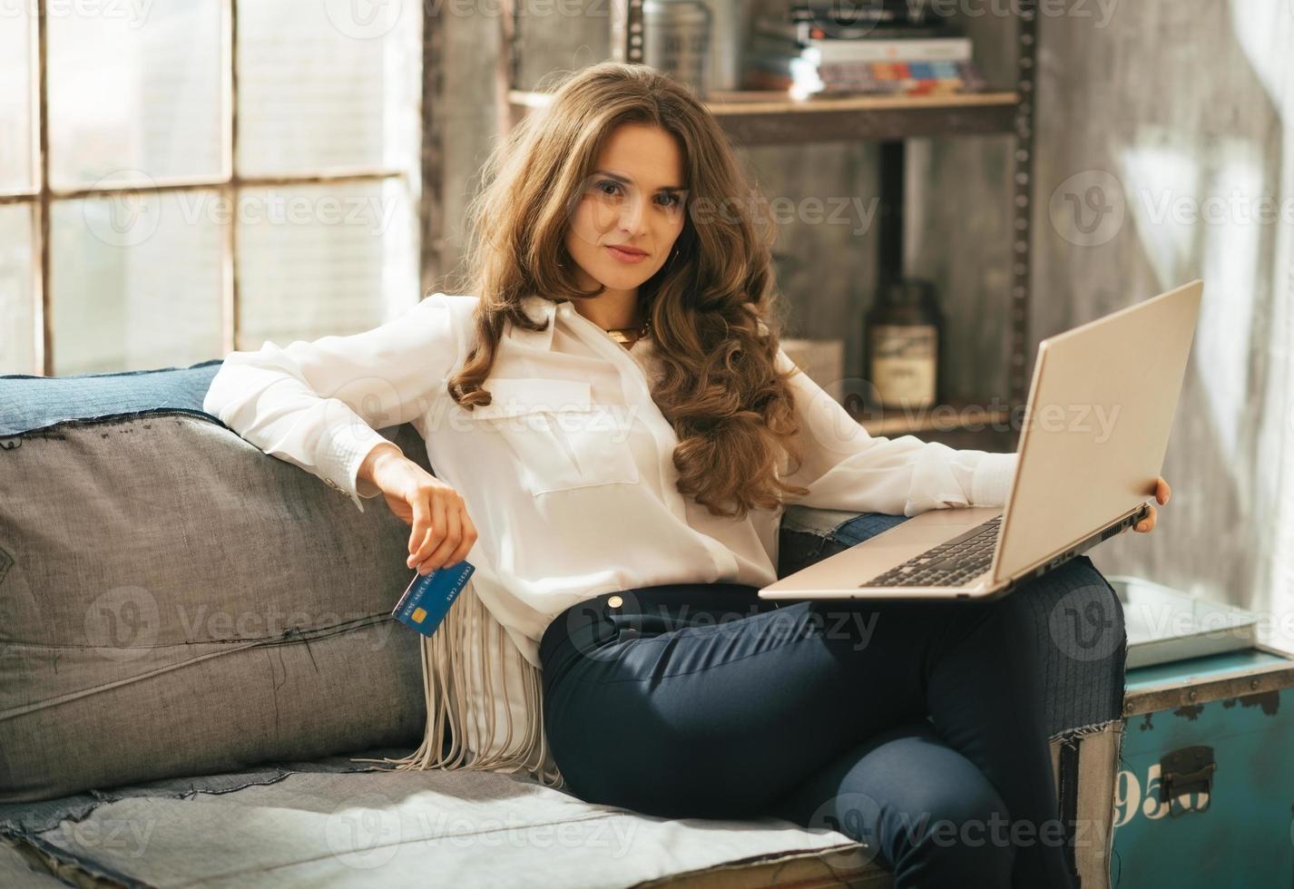 Ritratto di giovane donna con carta di credito e laptop foto
