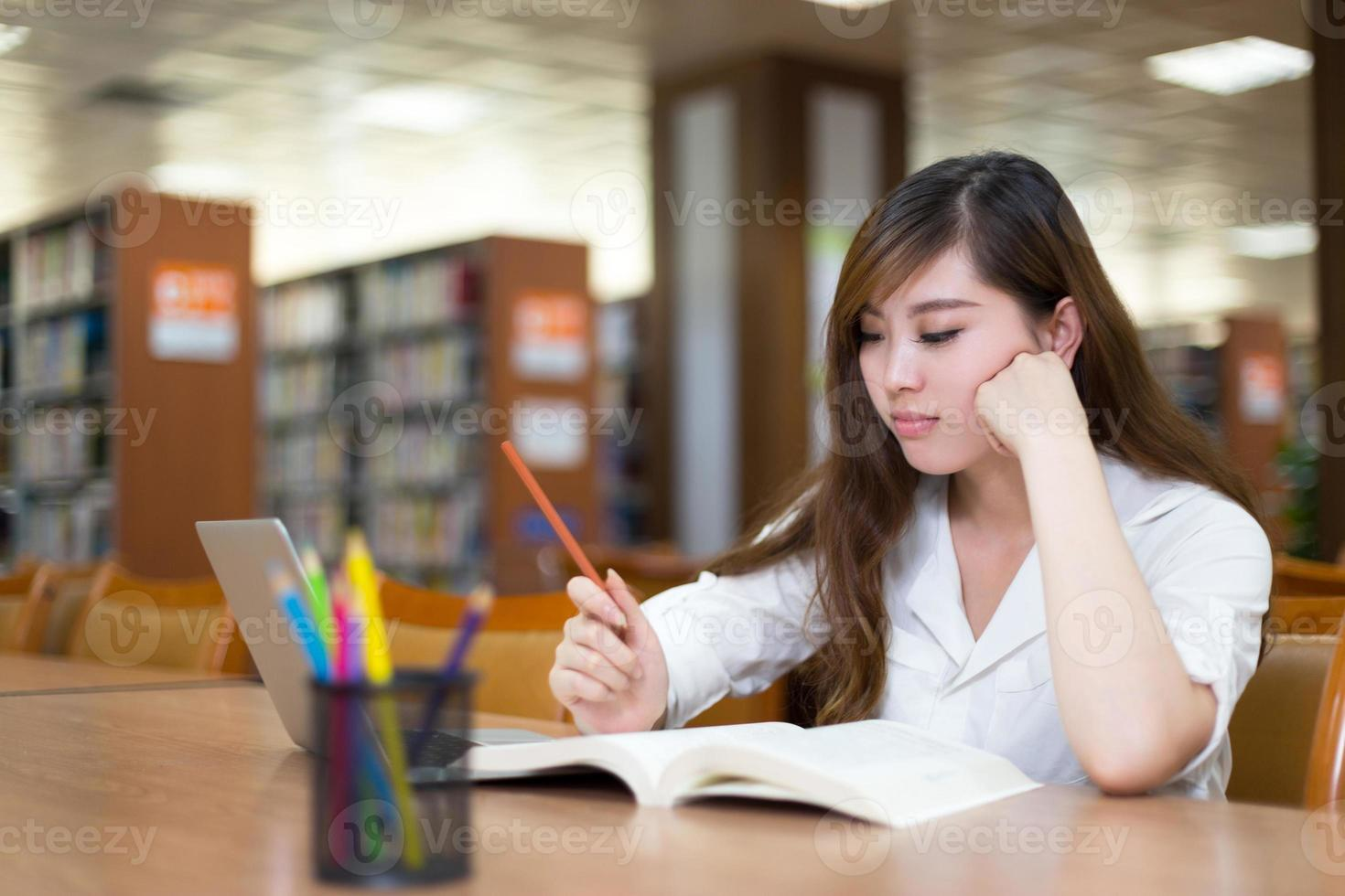 bella studentessa asiatica che utilizza computer portatile per lo studio nella biblioteca foto