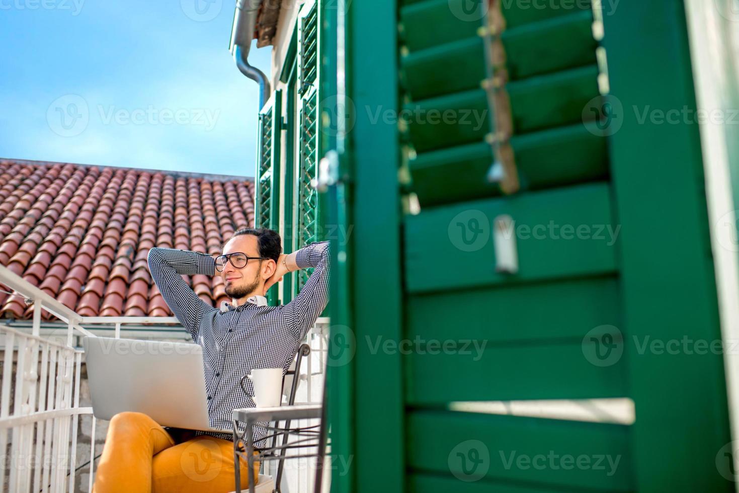 uomo con il portatile sul balcone foto