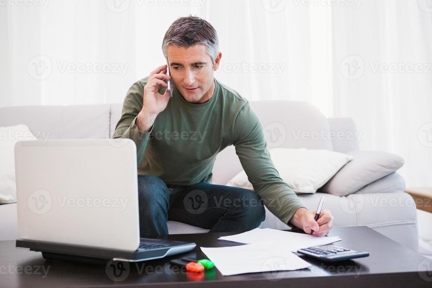 uomo con il portatile telefonando e prendendo appunti foto