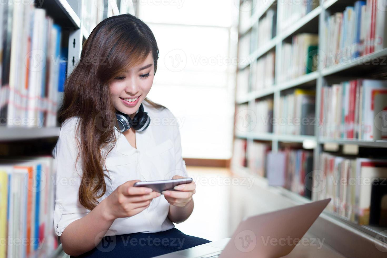 bella studentessa asiatica che per mezzo del computer portatile e del telefono cellulare foto