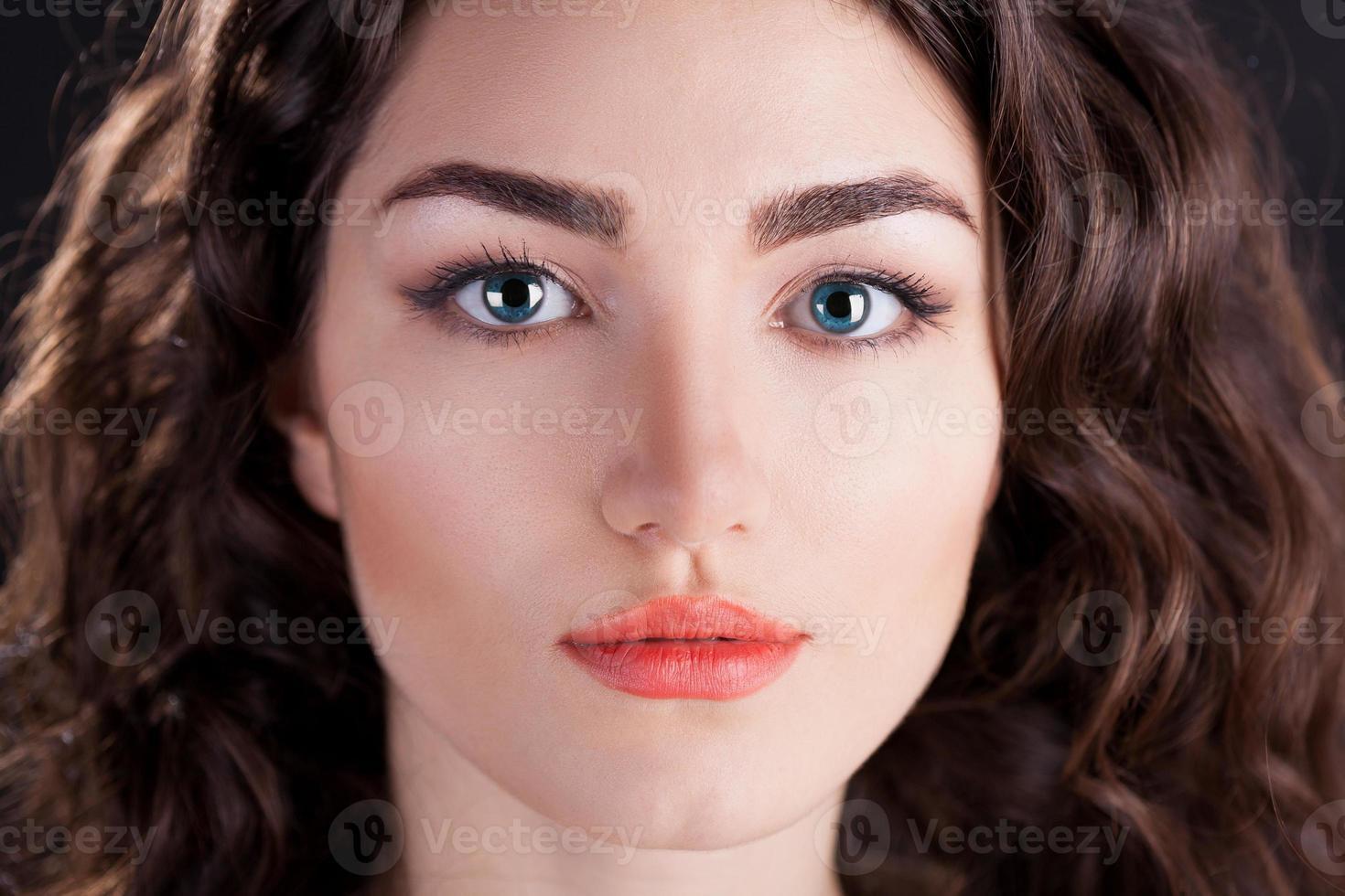 viso serio con lenti a contatto blu, sfondo nero foto