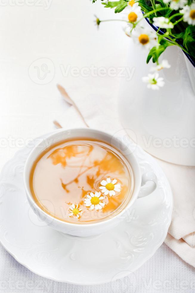 tisana di camomilla in una tazza bianca con foto