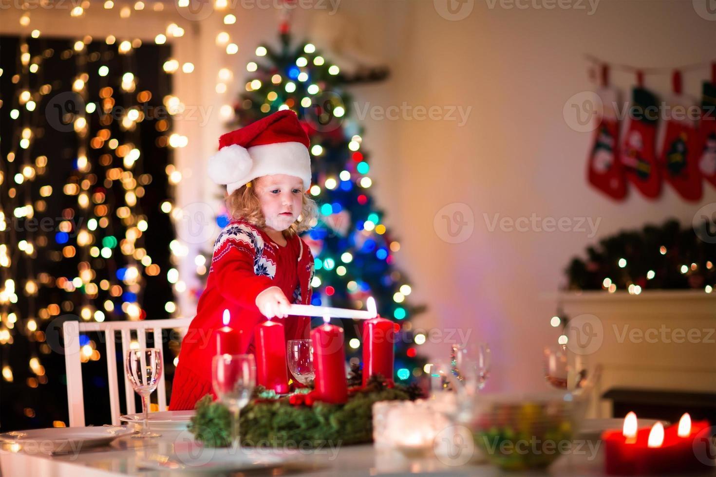 bambino a cena di Natale in famiglia a casa foto