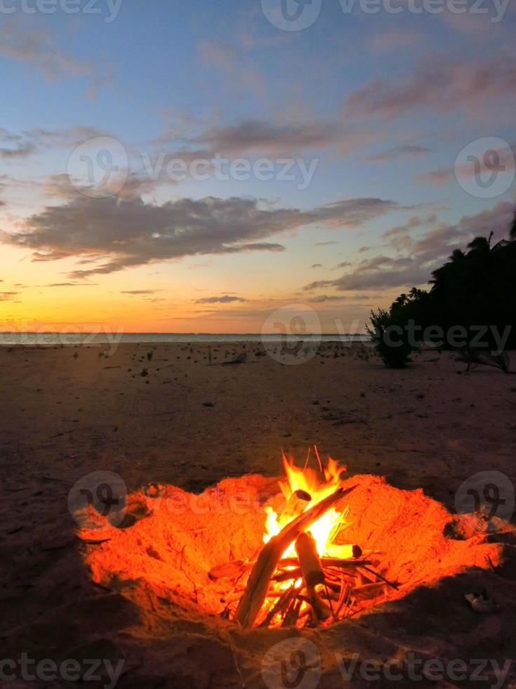 fuoco sulla spiaggia al tramonto nel tuamotus, sud pacifico. foto