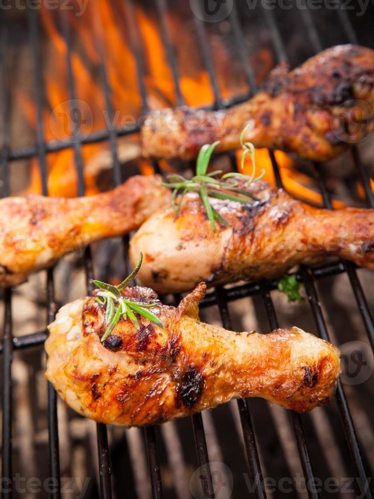 cosce di pollo che cucinano nella buca alla griglia del fuoco aperto foto