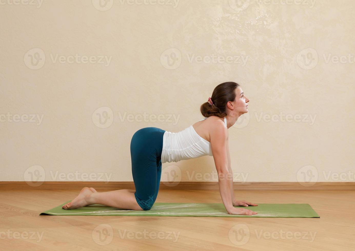 donna caucasica sta praticando yoga in studio (bidalasana) foto