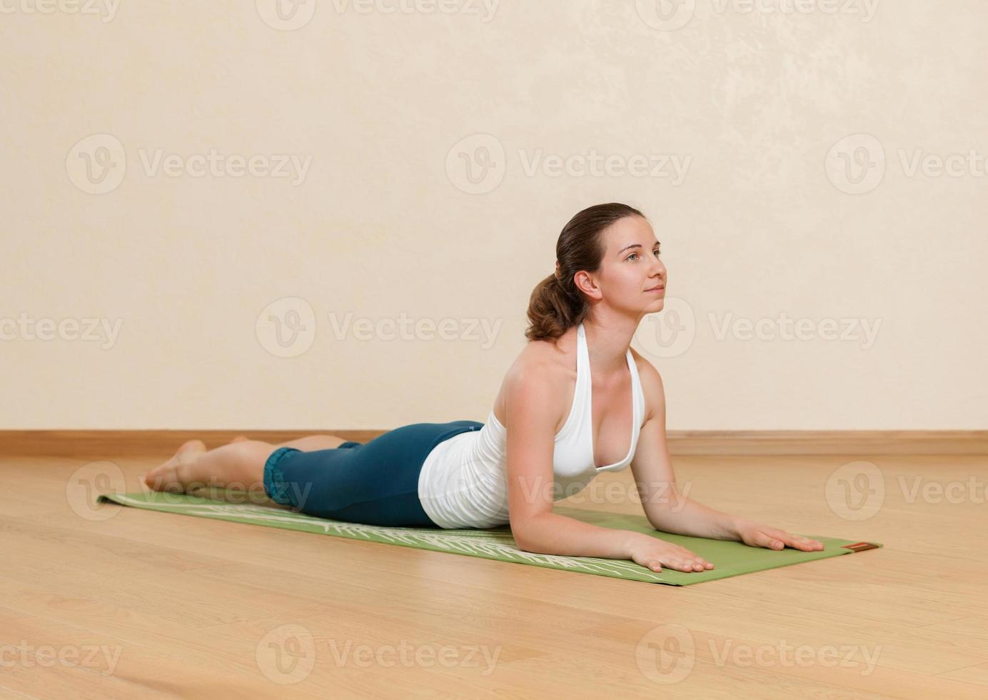 donna caucasica sta praticando yoga in studio (bkhudzhangasana) foto