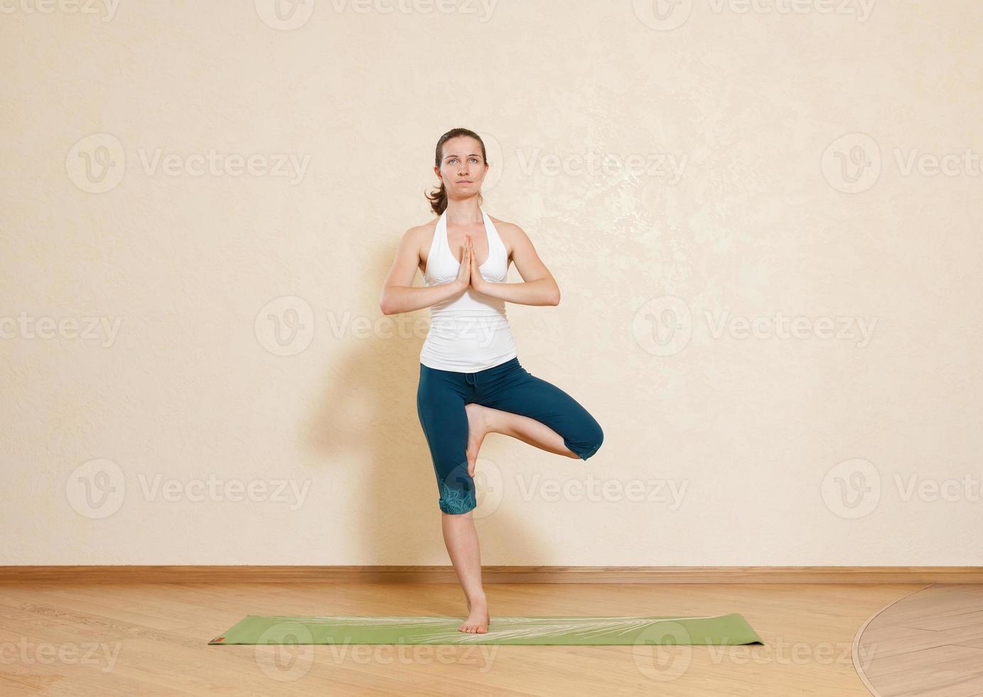 donna caucasica sta praticando yoga in studio (vrikshasana) foto