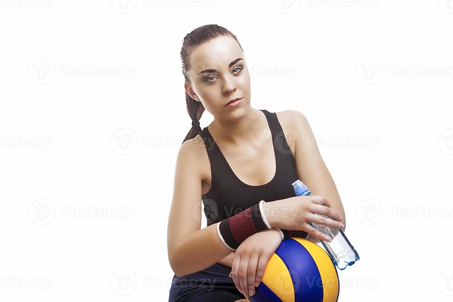 atleta di pallavolo femminile caucasico esaurito che si siede con la bottiglia di acqua foto