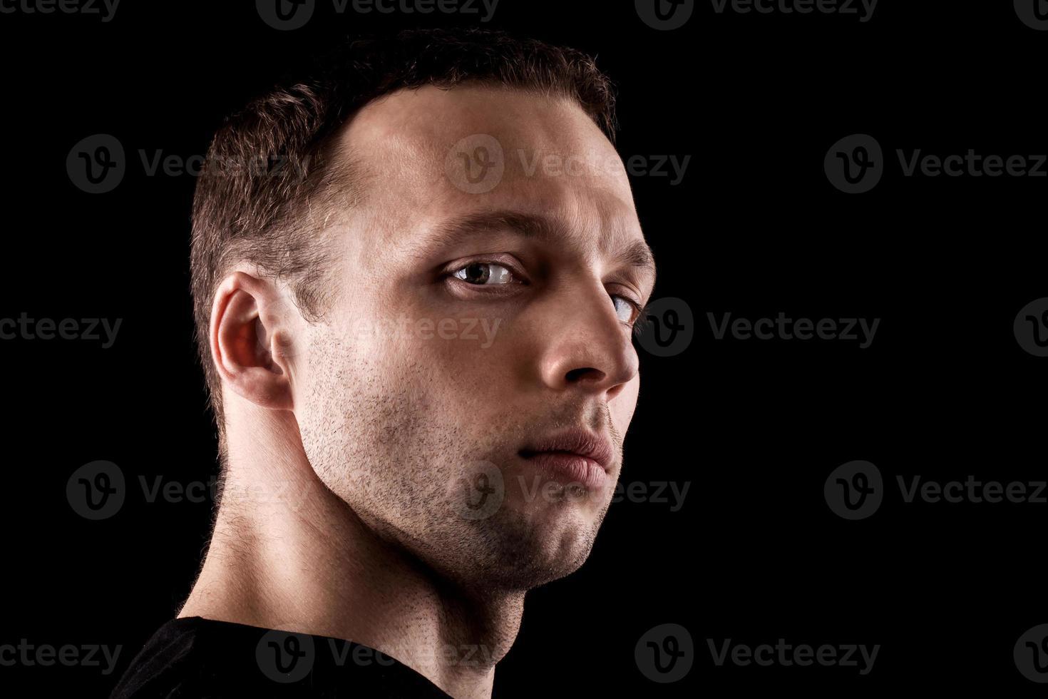 ritratto di giovane uomo caucasico altero. faccia del primo piano isolata sul nero foto