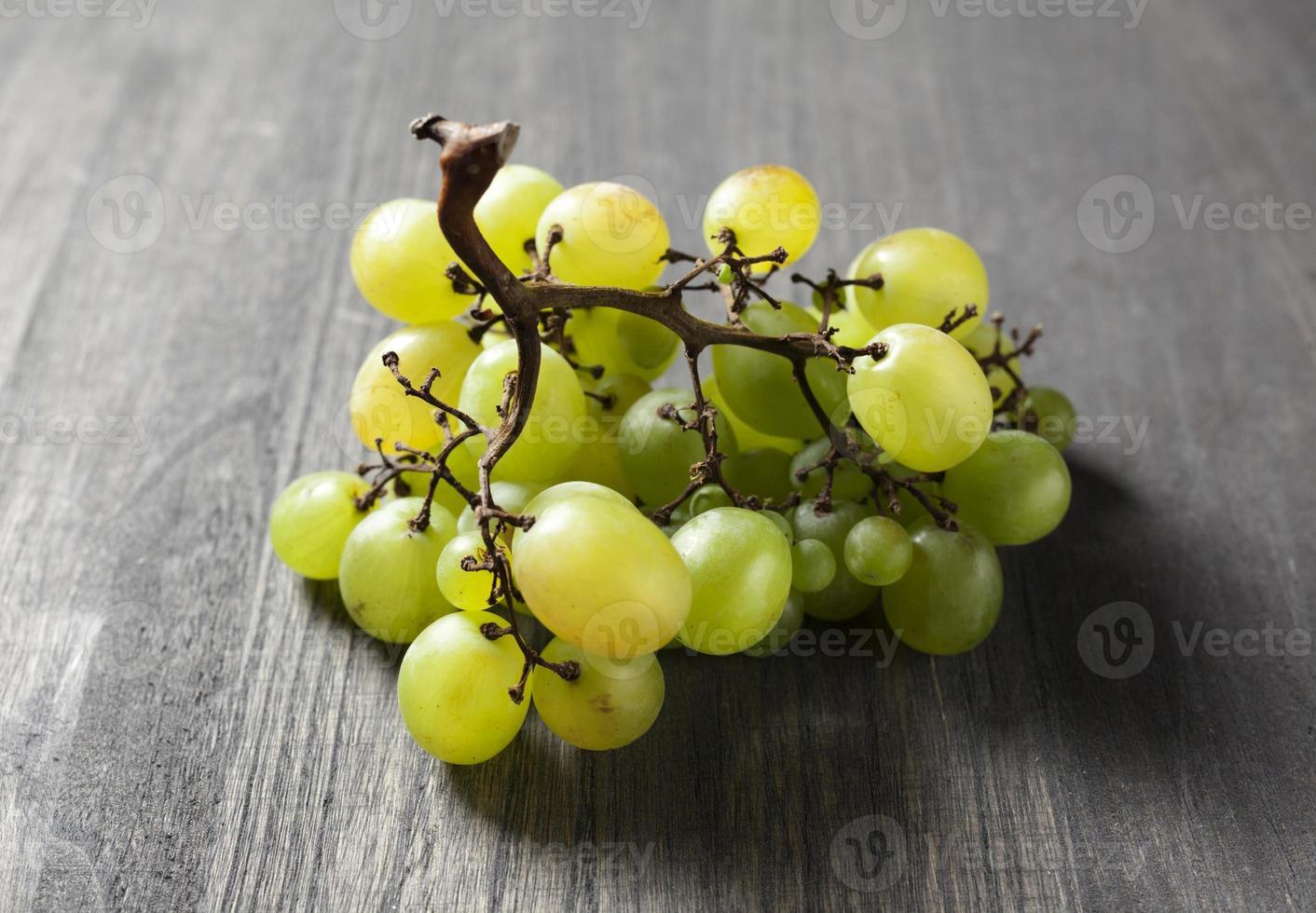 uva verde su un tavolo di legno foto