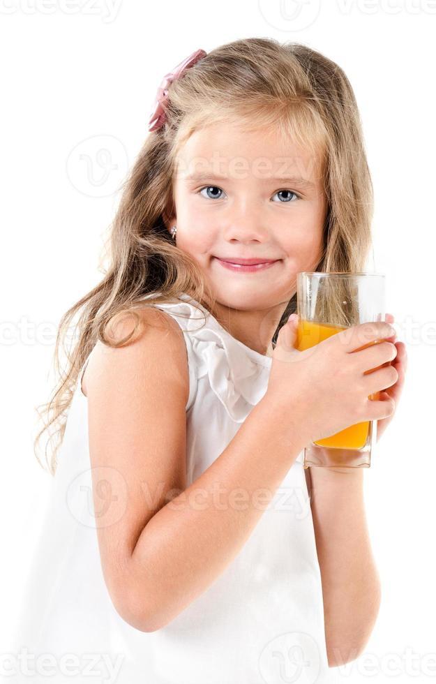 bambina carina sorridente con un bicchiere di succo foto