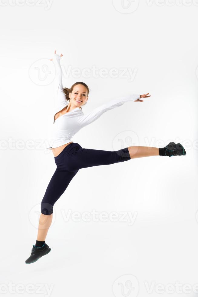 giovane donna che salta con i vestiti di esercitazione (isolati su bianco) foto