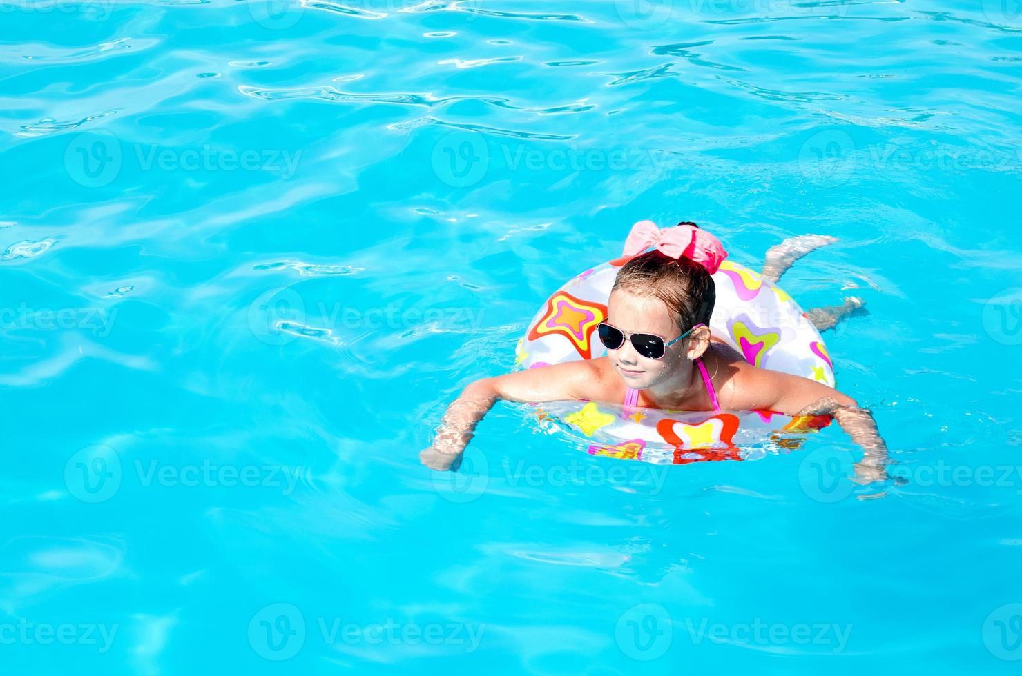 bambina sorridente in piscina foto