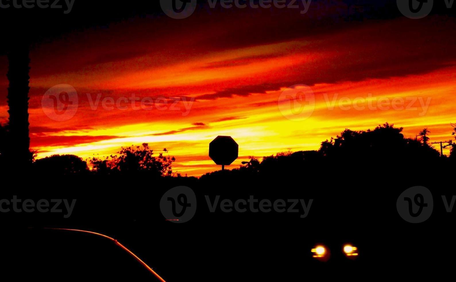 tramonto con segnale di stop che si staglia contro il cielo rosso fuoco foto