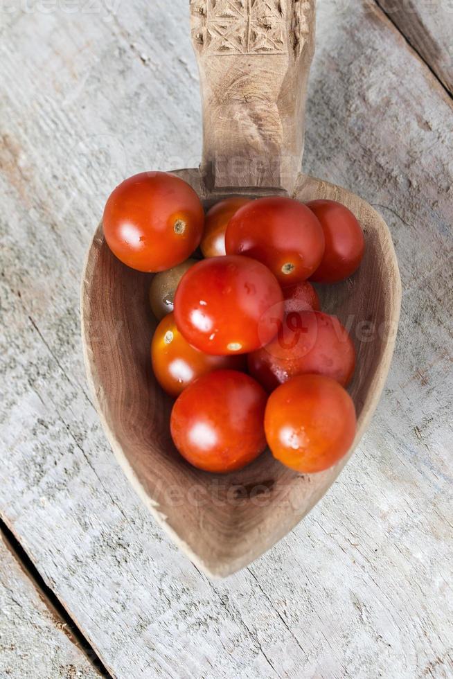 pomodori ciliegia in un cucchiaio sopra fondo di legno foto