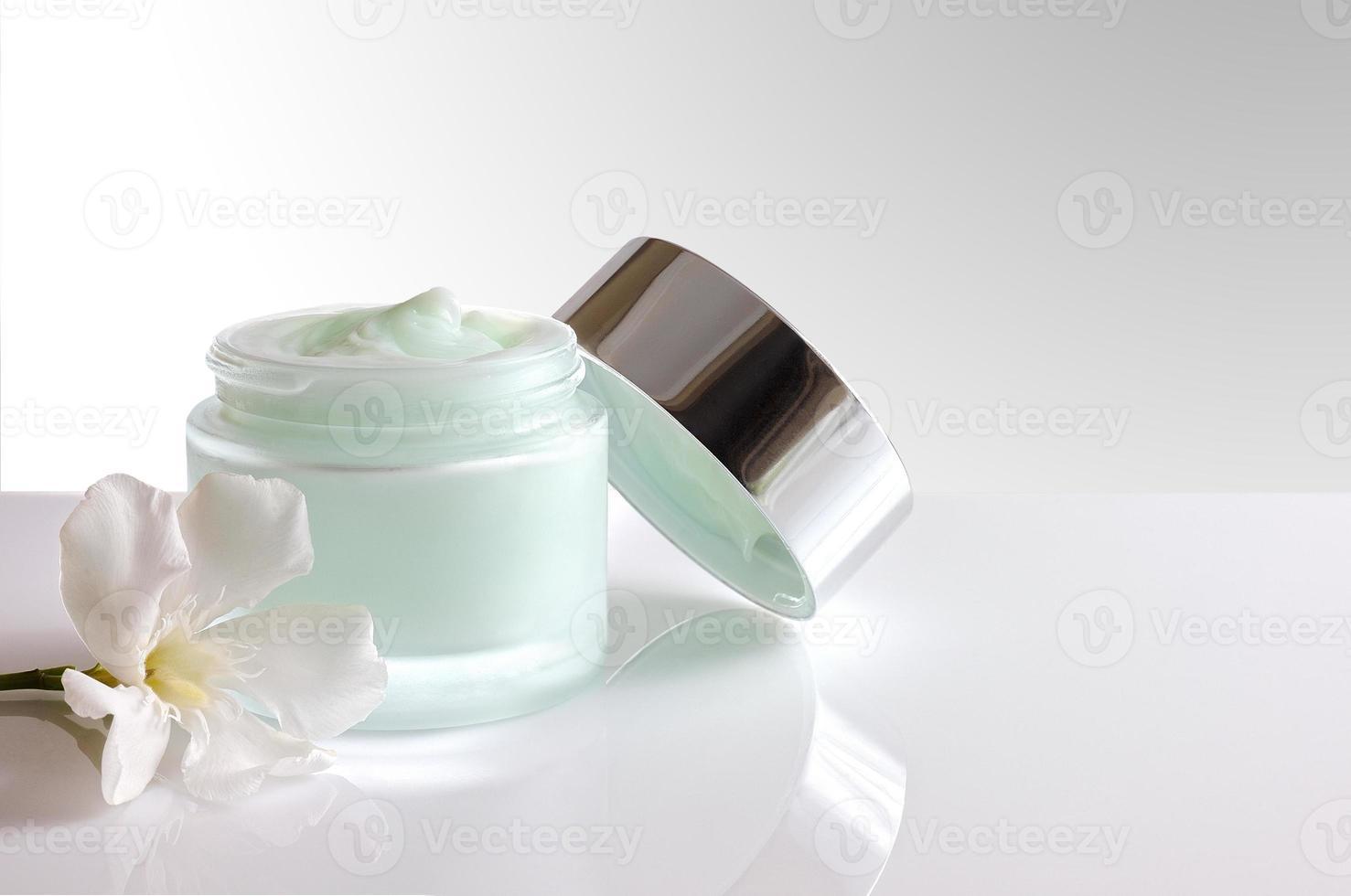vasetto di crema aperto con vista frontale coperchio isolato foto