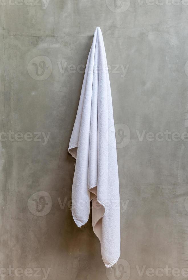 asciugamano bianco è appeso a una gruccia con muro di cemento foto