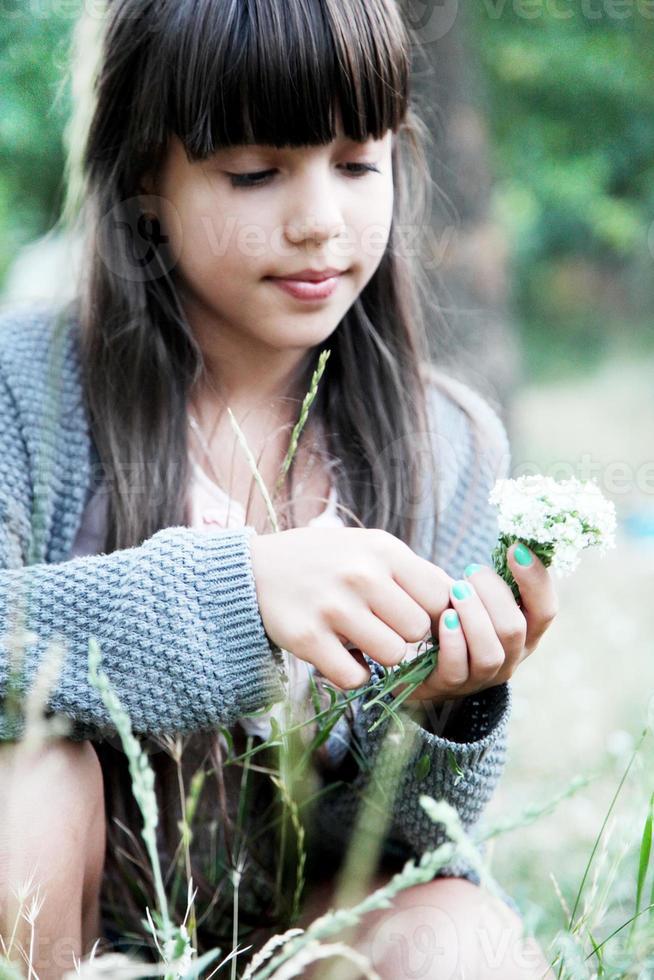ritratti di una ragazza nel parco con fiori foto