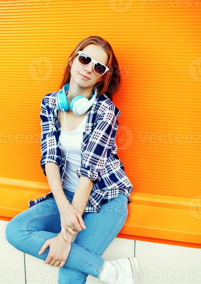 bella ragazza in occhiali da sole e cuffie contro il colorato o foto