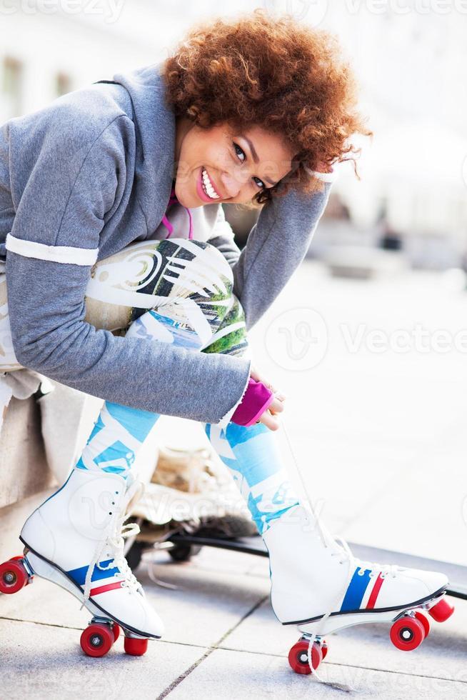 donna che mette sui pattini di rullo all'aperto foto