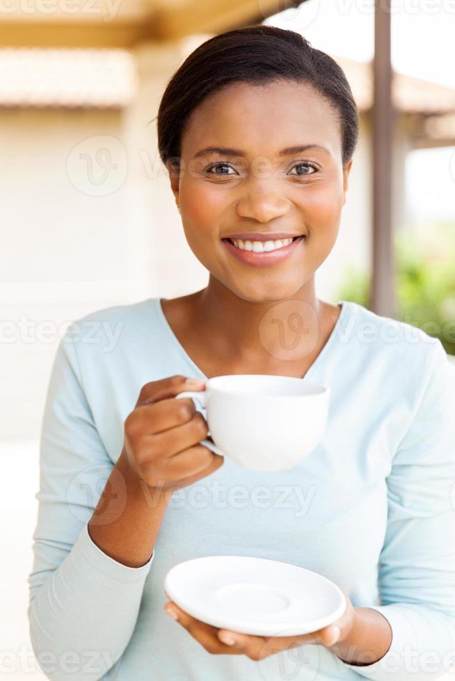 giovane donna africana che beve caffè foto