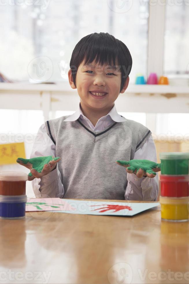 ritratto della pittura sorridente del dito dello scolaro nella classe di arte, Pechino foto